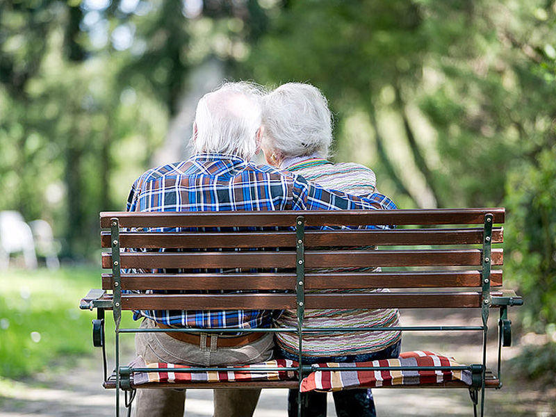 Ein alter Mann und eine alte Frau sitzen Arm in Arm auf einer Parkbank