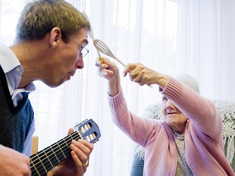 Ein Mann mit Gitarre musiziert mit einer älteren Dame.